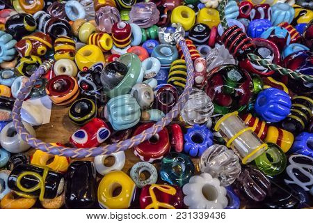Bright Background Of Jewelry. A Lot Of Different Colors Of Glass And Ceramic Beads For Bracelets And