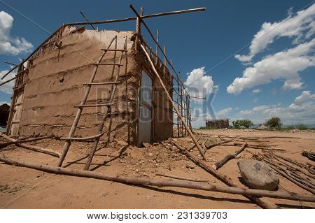 Construction Of A Poor Clay Hut: The Wooden Slats Stack The Walls Covered With Orange Clay, Africa.
