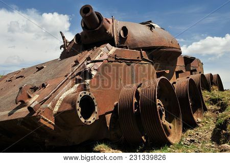 Old, Ancient Metal Tank With A Short Round Barrel And A Small Cabin On A Blue Sky Background With Cl