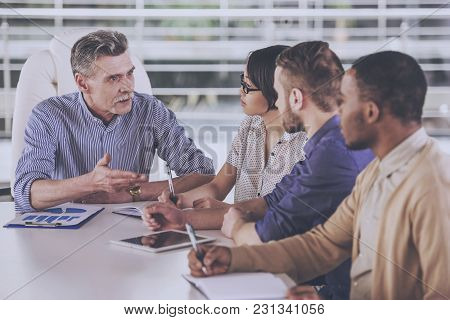 Group Of Business People Having Meeting In Office.