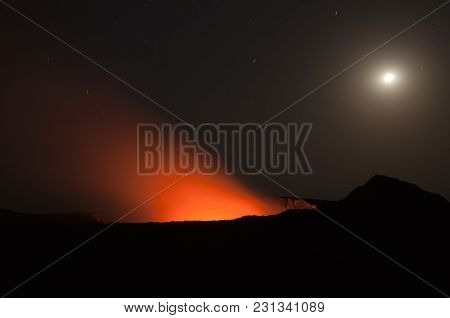 Burning Muzzle Of The Ertha Volcano, Night Photography, A Fiery Wall Bright Red Against The Black Sk