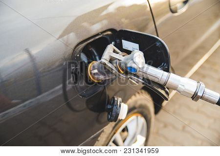 Car Fuel Up With Gas. Close Up Refueling Gun In The Neck Of The Tank