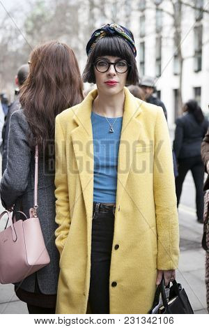London - February 18: Brunette Woman In A Yelllow Coat  And Stylish Glasses Outside Somerset House D
