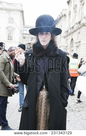 London - February 18: Stylish Man In Black Coat With Fur Coat In High Hat Smoking Cigarette During L