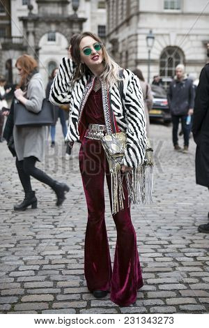 London - February 18: Stylish Blond Woman In White Black Furs Coat And Burgundy Jumpsuit Wearing Gre