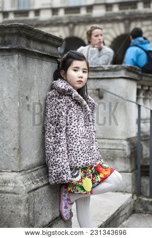 London - February 18: Brunette Little Girl In White Furs Artificial Coat Poses For Photogrpaher Outs