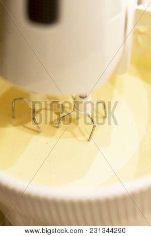 A Kitchen Mixer With Yellow Egg Yolks Mixed With Sugar.