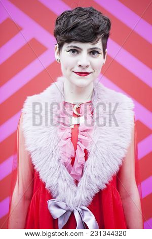 London - February 18: Smiley Woman In Red Dress With Fur Colar Poses For Photographers With Silver R