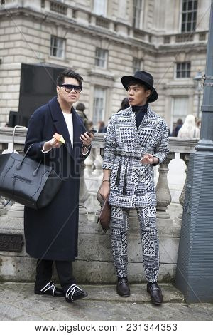 London - February 18: Serious Stylish Men In Hat And Suit  Poses For Photographers With Silver Rings