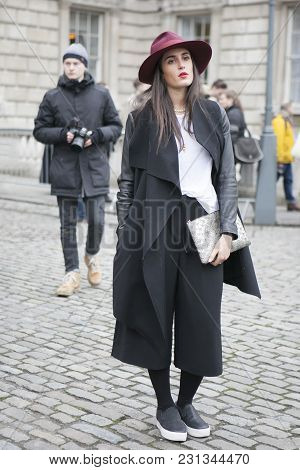 London - February 18: Blond Woman In Black Coat And Violet Hat Poses For Photographers With Silver R