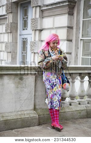 London - February 18: Woman With Pink Hair In Colar Coat And  Poses For Photographers With Silver Ri