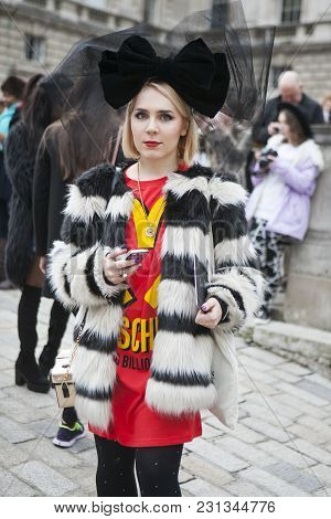 London - February 18: Blond Woman In White And Black Fur Coat And Red Dress  Poses For Photographers