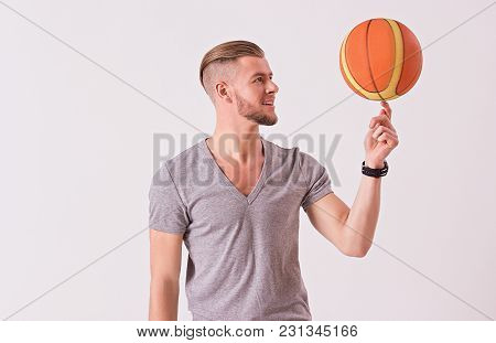Bearded Hipster In T-shirt Spinning Basketball Ball On Index Finger And Smiling While Isolated On Wh
