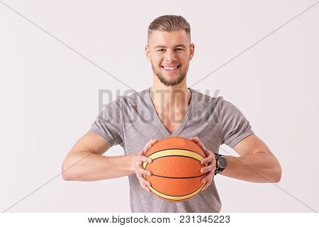 Portrait Of Cheerful Basketball Player Carrying Ball In Hands And Smiling While Isolated On White Ba