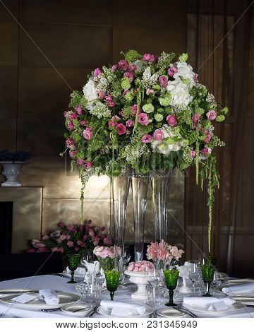Hydrangea And Pink Ranunculus Floral Arrangement In Vase As Decoration Of Wedding Dinner With Green