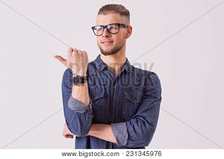 Studio Shot Of Young Male Student In Eyewear Showing To Copy Space And Smiling While Standing Agains