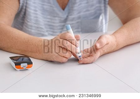 Elderly woman with diabetes measuring level of blood sugar at home, closeup
