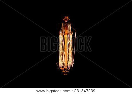 Low Light Of Vintage Light Bulb Filament Isolated On Black Background