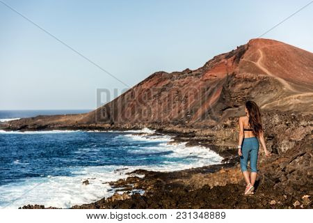 Mountain fitness model girl walking on trail path in volcanic rocks, outdoor adventure. Fit healthy active lifestyle person enjoying outdoors.