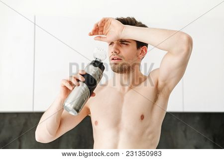 Portrait of a serious naked man sportsman standing in kitchen in home looking aside drinking water.