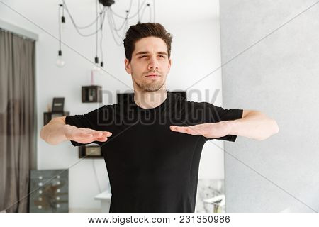 Photo of handsome young man standing in home indoors. Looking aside make sport exercises.