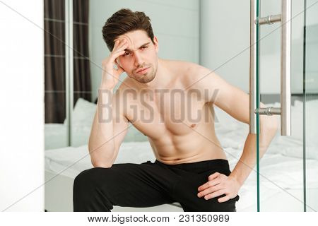 Portrait of a serious naked man sitting on bed in home looking aside.