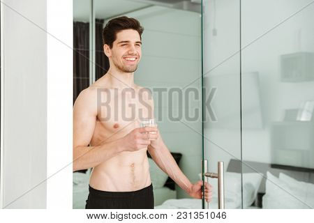 Portrait of a cheerful naked man standing in home indoors looking aside drinking water.