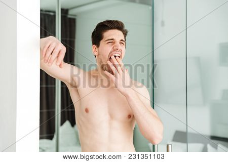 Portrait of a sleepy yawning naked man standing in home looking aside.