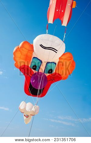 a kite in the shape of a clown face flying on the blue sky