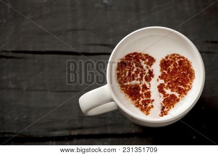 high-angle shot of a white ceramic cup of cappuccino with a broken heart drawn with cocoa powder on its milk foam, on a dark gray rustic wooden table