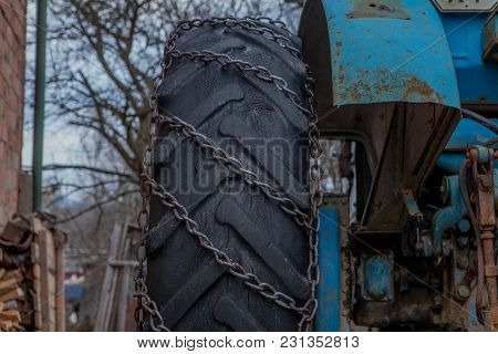 Tractor Equipped With Snow Chains. Winter Concept.