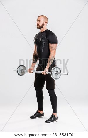 Full lenght image of healthy young sportsman. Looking aside make sports exercises with barbell.