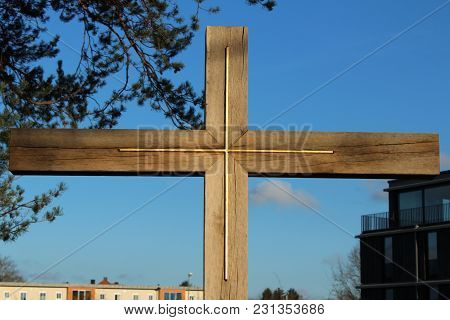 Christian Symbol Cross For Believers In City Park Between Trees.