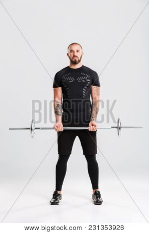 Full length photo of strong young sportsman. Looking camera make sports exercises with barbell.