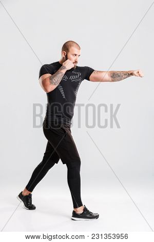 Image of strong healthy young sportsman boxer. Looking aside make sports exercises.