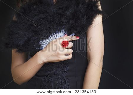 Female Hands With A Red Ring Holding A Black Fan. Woman In Black Dress On Black Background