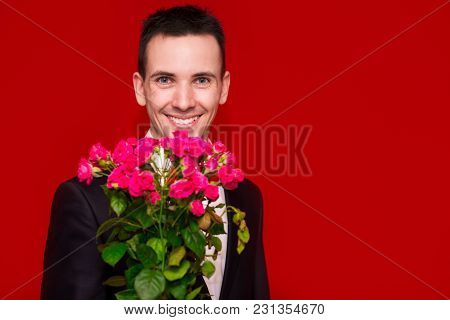 Stylish Man In Suit Holding A Bouquet Of Flowers With Red Background