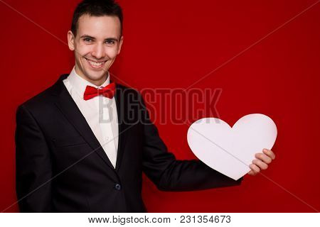 Stylish Man In Suit Hold White Paper Heart, With Red Background. Valentines Day Composition