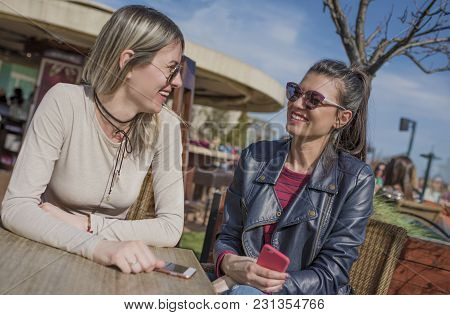 Two Beautiful Young Women Having Fun Outdoors While Using Their Smartphones