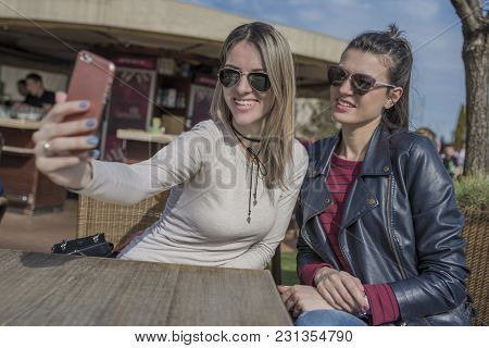 Two Beautiful Young Women Having Fun Outdoors While Using Their Smartphones, Taking Selfie