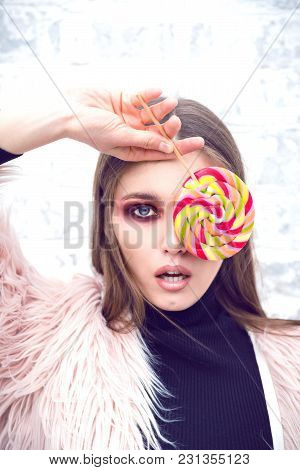 A Girl With Lollipop. Girl In Casual Clothes. Brick Wall Background. Gloomy Makeup. Fashionable Woma