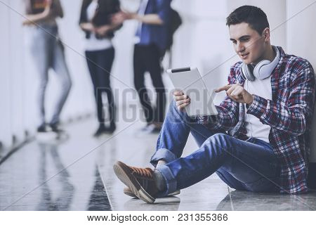 Male Handsome Young Student Using A Tablet.