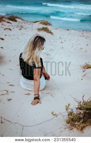 Woman Sitting In White Sand Dune Landscape On The Atlantic Coastline. Waves Hitting Coast In Backgro
