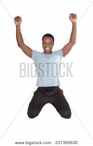 A Young Handsome African American Man Kneeling On The Floor With His Fists And Smiling Of Victory An