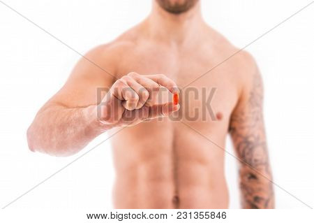 Muscular Young Man Holding Orange Pill Isolated On White Background.