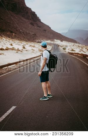 Traveler With Backpack Standing In The Center Of An Epic Winding Road. Huge Volcanic Mountains In Th