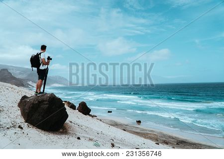 Traveler With Camera Staying On The Black Volcanic Boulder And Admiring Unusual Barren Landscape Of