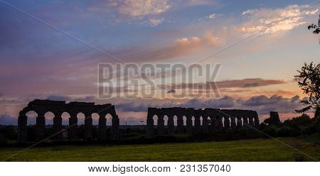 View Of Ancient Roman Aqueduct Ruins In Rome Countryside At Sunset