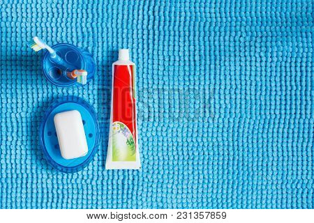 Blue Glass With Toothbrushes, Tube Of Toothpaste And Soap Dish With White Soap.