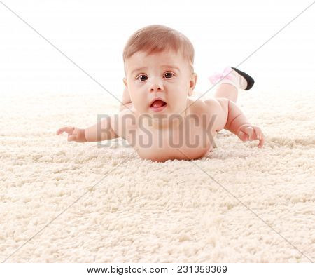The Baby Is Lying On Her Stomach On The Carpet In The Room And Smiling On White Background